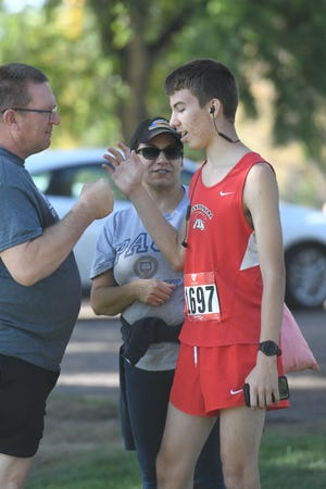 William Page (right) talks to his parents, father Dennis (left) and mother Sheryl, prior to racing in the Central Invitational on Saturday at the Elmwood Golf Course Short Nine.