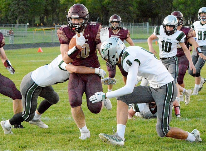 Milbank Area's Marshall Voeltz shakes off the tackle attempt of Clark-Willow Lake defenders Cole Brenden (left) and Mitchell Larson to score a touchdown during their high school football game Friday night in Milbank. The host Bulldogs celebrated their homecoming with a 34-13 win.