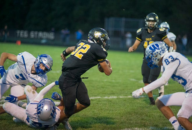 Colonel Crawford's Matt Clinard shakes off Wynford's Kohen Keith for extra yardage.