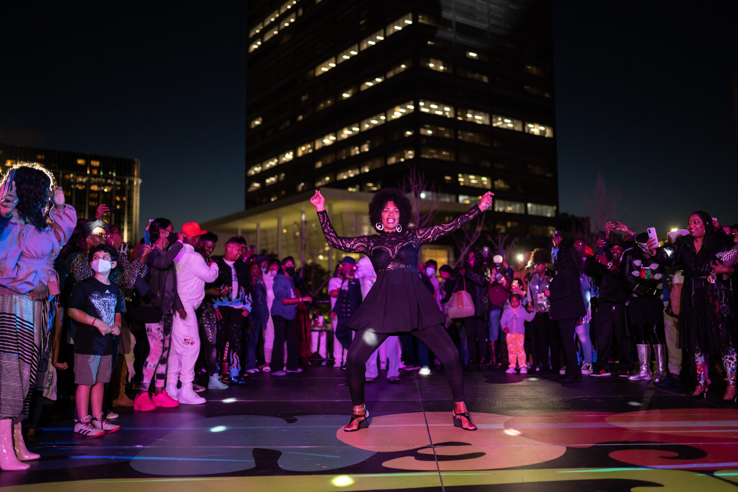 """LaWanda Gray-Anner kicks off the dance line as others wait for their moment to shine while taking part in """"The Scene with Nat Morris and Friends"""" as part of the DLECTRICITY event at Beacon Park in downtown Detroit on September 24, 2021. The event featured former dancers from Detroit's historic daily dance show that aired on WGPR TV, the first African-American owned and operated television station licensed by the FCC in The United States from 1975-1987, taking part in an open dance floor. The Scene looked to attempt Detroit's longest dance line giving each dancer 30 seconds to keep it moving."""