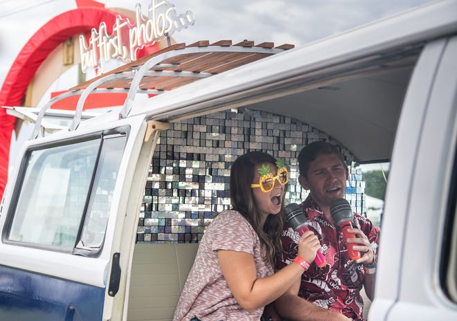 Jaime Myers and Drew Myers pretend to sing inside a van-style photo booth at the Americana Music Triangle Experience area during the first day of the Pilgrimage Music & Cultural Festival at the Park in Harlinsdale in Franklin, Tenn., Saturday, Sept. 25, 2021.