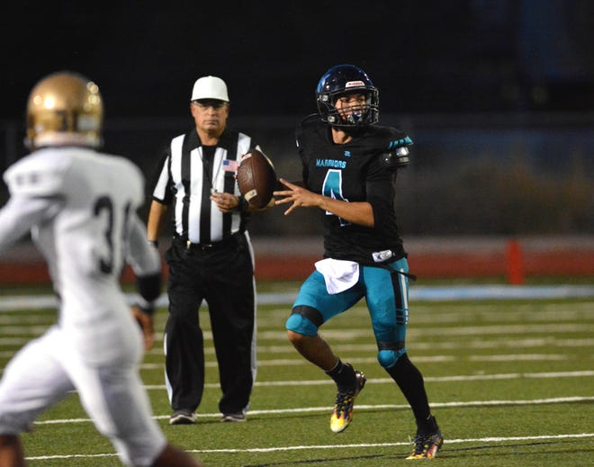Quarterback Julian Cobos for Santa Teresa rolls to his right looking for an open receiver as the Desert Warriors took on Ruidoso Friday, Sept. 24, 2021.