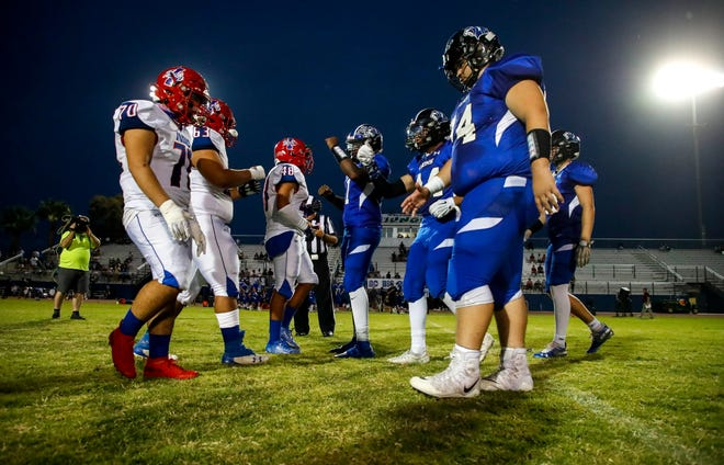 Indio and Cathedral City captains shake hands after the coin toss before the first quarter of their game at Cathedral City High School, Friday, Sept. 24, 2021, in Cathedral City, Calif.