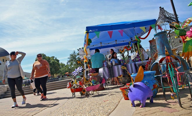 People walk by a vendor booth near the San Angelo Museum of Fine Arts during the inaugural Family Fiestas Patrias event Saturday, Sept. 25, 2021.
