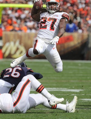 Cleveland Browns running back Kareem Hunt leaps over Chicago Deon Bush on Sunday, Sept. 26, 2021 in Cleveland, Ohio, at FirstEnergy Stadium. The Browns won the game 26-6.  [Phil Masturzo/ Beacon Journal]