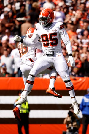 Cleveland Browns defensive end Myles Garrett (95) and linebacker Jeremiah Owusu-Koramoah (28) celebrate after sacking Chicago Bears quarterback Justin Fields (1) during an NFL football game, Sunday, Sept. 26, 2021, in Cleveland. (AP Photo/Kirk Irwin)