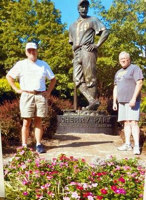 """Lauren Hartley (izquierda) y Stan Brussel junto a una estatua """"Poderoso Casey"""" En Cherry Park en Rock Hill, SC"""