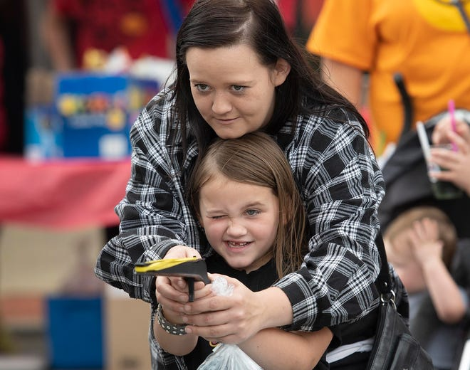 Jasmine Herrmann, 6, aims a rubber band gun with a little help from her mom, Kellie Gilmore, during the Ellwood City Fall Fest and Car Cruise on Saturday.