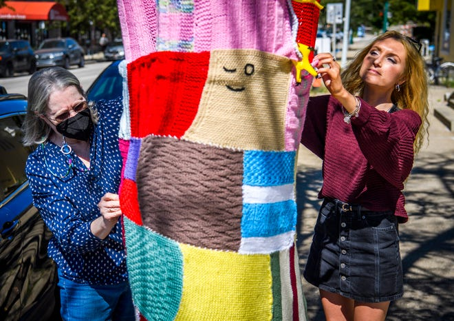 Indiana University sophomore Macee Long, right, and Mary Lostutter work on knitting a sweater on a tree on the northeast corner of 6th Street and College Avenue for the Wrapped in Love event benefitting Bloomington's Middle Way House on Friday, September 24, 2021.