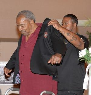 Willie Spencer Jr. puts a black jacket on his father, Willie Spencer Sr., during the 2019 Massillon Pro Football Celebration.