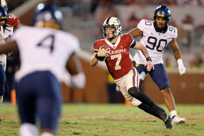 Oklahoma's Spencer Rattler (7) runs away from West Virginia defenders during 16-13 win Saturday night.