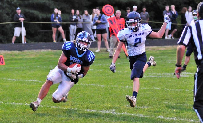 York's Hayden Henriksen, left, slides into the end zone after catching a touchdown pass from QB Luke Doughty, one of five TDs Henriksen scored in his team's 55-14 win over Westbrook on Saturday. Westbrook's Collin Allen is too late to break up the play.