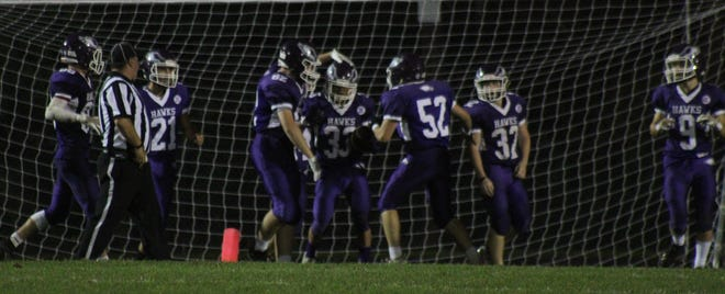 Members of the Marshwood High School football team surround running back Emmanuel Poe (33) after his 76-yard touchdown run in Saturday's 40-7 win over South Portland.