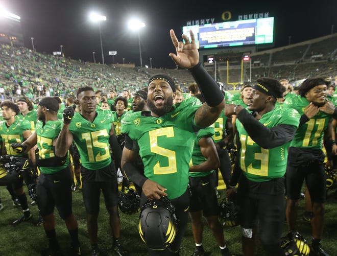 Oregon's Kayvon Thibodeaux  celebrates with teammates after the win over Arizona in their first Pac-12 game of the season.