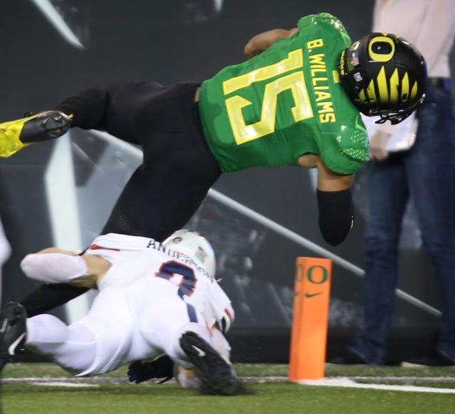 Oregon's Bennett Williams dives into the end zone for a touchdown after running back an inception late in the fourth quarter against Arizona.