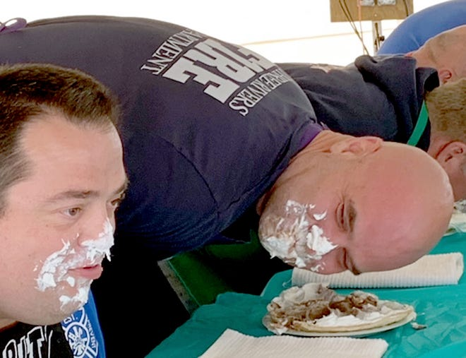 Travis McGahn checks progress made by competitor Josh Shook during a pie-eating contest Saturday at the St. Joseph County Grange Fair.