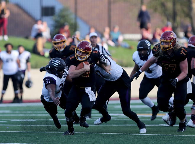 Northern State quarterback Hunter Trautman breaks away from several USF defenders during the first quarter of Saturday's game at Dacotah Bank Stadium. American News photo by Jenna Ortiz, taken 09/25/2021.