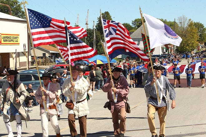 The Sons of the American Revolution make their way down Mitchell's Main St. during the Persimmon Festival Parade Saturday.