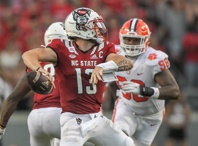 NC State quarterback Devin Leary (13) passes near Clemson defensive end Myles Murphy (98) during the fourth quarter at Carter-Finley Stadium in Raleigh, N.C., September 25, 2021.  The Tigers lost 27-21 in two overtimes game at Carter-Finley Stadium in Raleigh, N.C., September 25, 2021. Leary  was 32-44 for 238  yards and four touchdown passes.