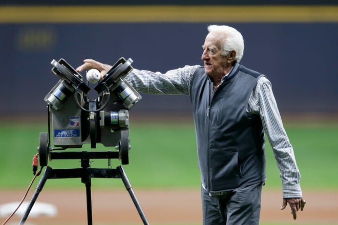 Brewers radio announcer Bob Uecker throws out the first pitch using a pitching machine as he is honored for 50 years of broadcasting before the game at American Family Field Saturday.