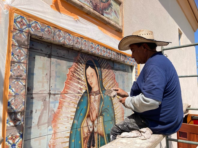A tile worker installs a COVID-themed mural at Padre Serra Parish in Camarillo. The artwork was publicly unveiled Sunday, Sept. 26, 2021.