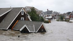 Floodwaters surround homes near the Mantoloking Bridge the morning after hybrid storm Sandy rolled through, Tuesday, Oct. 30, 2012, in Mantoloking, N.J.