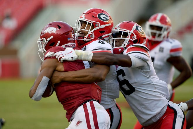 Georgia defenders Nolan Smith (4) and Lewis Cine (16) tackle Arkansas running back Rakeem Boyd during an college football game in Fayetteville, Ark. Saturday, Sept. 26, 2020. (AP Photo/Michael Woods)