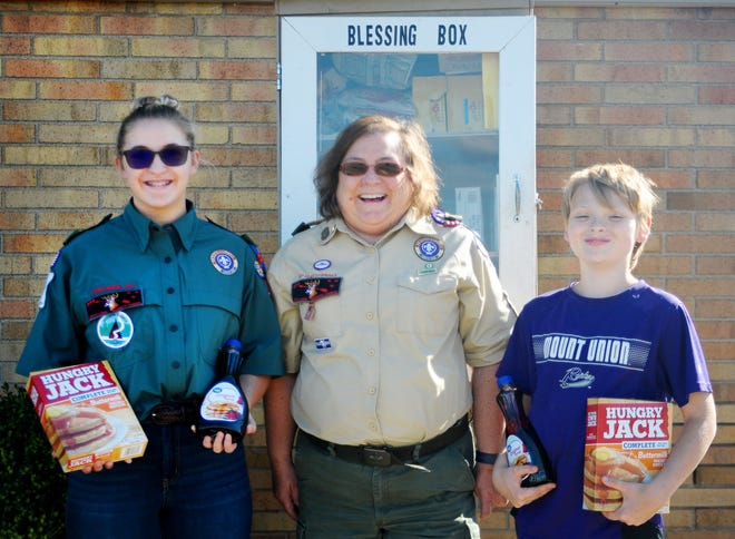 Mikayla Robinson, left, Kim Moles and Kyler Loy, 12, right, hold items donated as part of a Reverse Breakfast event that Buckeye Council's Alliance Area Troop 177 and Venture Crew 177 conducted Sunday, Sept. 26, 2021, at a Blessing Box outside Alliance City Health Department. Items in the box are available 24 hours a day, every day.