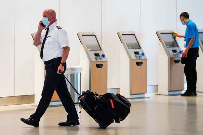 An American Airlines pilot walks past as airport contractor David Ramirez wipes down check-in kiosks with disinfectant at DFW International Airport Terminal A in 2020. The airline industry is in its biggest hiring push in decades for jobs across the board.