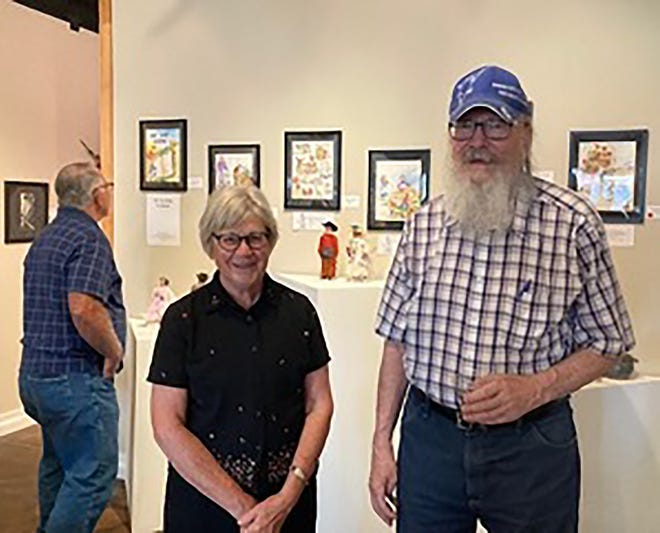 Artist Mary Anne Hendrix stands in front of her watercolors during her exhibit at the 2nd Avenue Art Guild in Dodge City. Beside her is Ford County Historical Society president Kent Stehlik.