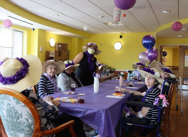 """St. John's residents on the Beyond Memory floor form a new club: The Purple Hat Society. The club started as a way to beat the """"COVID-19 blues,"""" and to encourage residents living with dementia to gather safely, socialize and partake in activities. The group meets once a month and decorated their own hats they wear around the St. John's campus."""