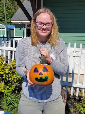 Volunteer Azline Maurals (Acton) from Sanford High School shows off her painted pumpkin, after picking it out at Seashore Trolley Museum's Pumpkin Patch.