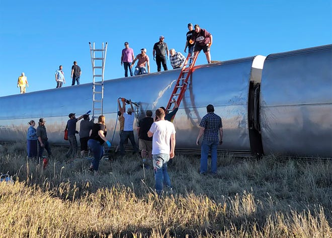 Local residents help passengers climb out of rail cars at the scene of Saturday's Amtrak derailment in north-central Montana.