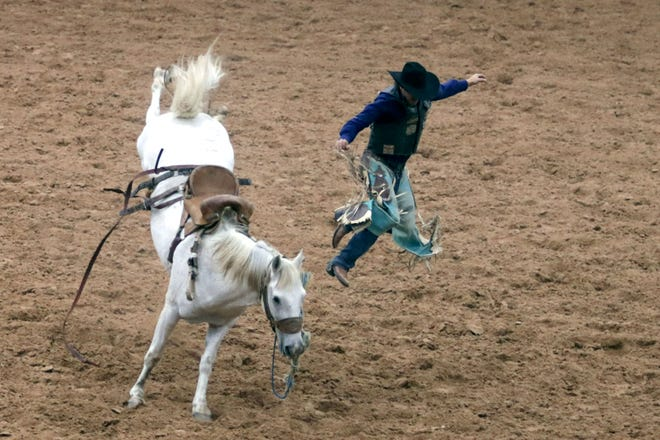 Jacob Lewis from Stephenville jumps clear from his horse during the bronc riding competition in the PRCA Rodeo on Saturday evening at the Tri-State Fair and Rodeo in Amarillo.