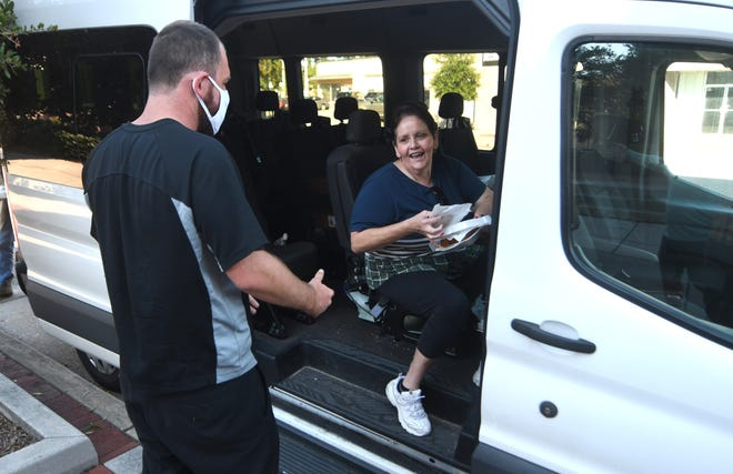 Sue Adkins, a street outreach worker with First Fruit Ministries, feeds members of the homeless community in front of the library in downtown Wilmington, N.C, Sunday, Sept. 26, 2021. The organization goes out to feed members of the homeless community several times a week.