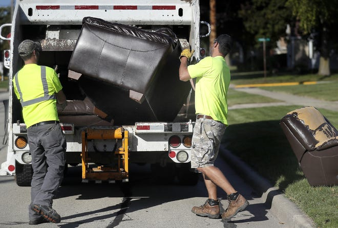 Little Chute public works employees Zach Gussert, left, and Tyler Nechodom pick up discarded furniture on Lincoln Avenue. The village prohibits anyone from scavenging items placed on the terrace without the permission of the owner.
