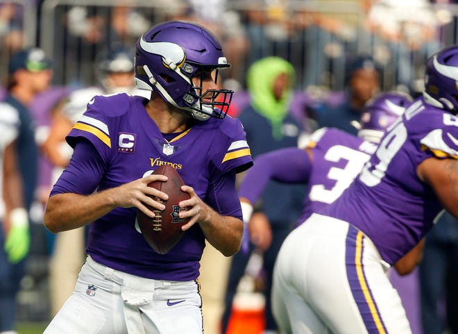 Minnesota Vikings quarterback Kirk Cousins, left, prepares to throw against the Seattle Seahawks in the first half of an NFL football game in Minneapolis, Sunday. (AP Photo/Bruce Kluckhohn)