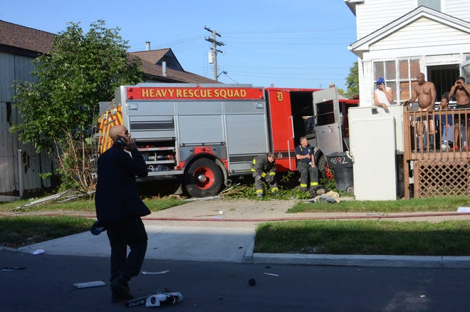 After colliding with a vehicle, a firetruck went through a fence and into a house on McClellan Street in Detroit on Monday, Sept. 27, 2021.