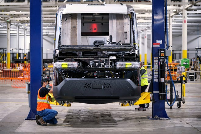 In Livonia, General Motors employee Anshul Shah attaches trim pieces on Sept. 24 onto the BrightDrop EV600, the company's first all-electric light commercial vehicle purpose-built for the delivery of goods and services