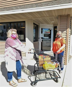 Newcap staff members Carrie Guarisco and Wendy Bain are seen with a shopping cart of food ready to delivered to a client on Monday. The agency has been doing contactless distribution since the start of the pandemic in March 2020. Newcap's pantry distributes food on Monday, but people in need on other days are not turned away.