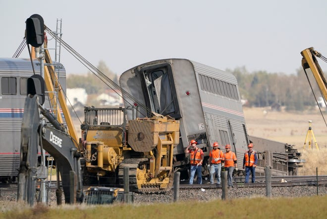 Workers walk Sunday, Sept. 26, 2021, next to an Amtrak train that derailed Saturday just west of Joplin, Mont. The westbound Empire Builder was en route to Seattle from Chicago, with two locomotives and 10 cars.