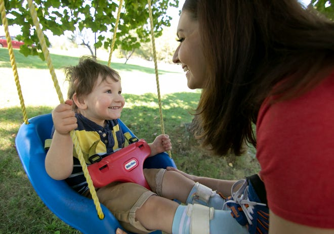 3-year-old Ethan Lambert plays on the yard swing with his mother Kassondra at their Pinckney home Monday, Sept. 27, 2021. A neurodegenerative condition known as KAND limits Ethan's mobility and speech.
