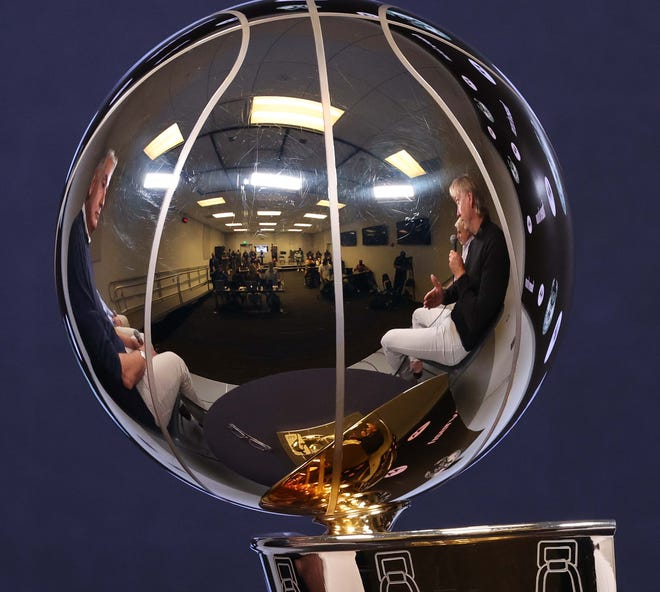 Milwaukee Bucks owners Marc Lasry, left, and Wes Edens are reflected in the Larry O'Brien Championship Trophy during media day Monday at Fiserv Forum.