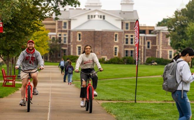University of South Dakota students ride bikes around the campus.