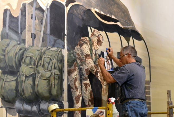 Michael Rosato works on a mural at the National Museum of the Marine Corps, which will feature Marine Corps history from 1976 to the wars in Iraq and Afghanistan, and is projected to open in 2025.