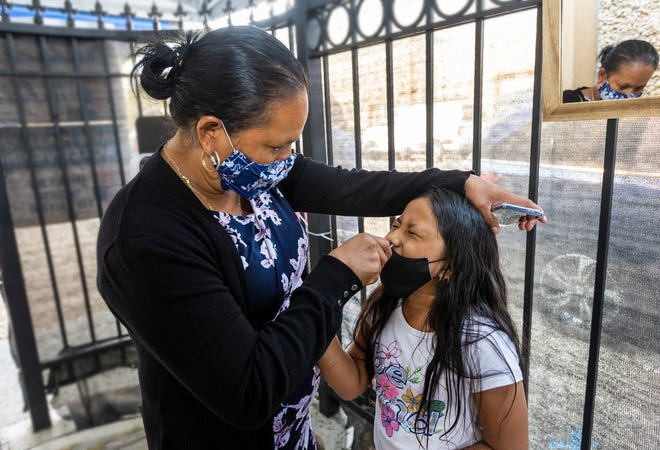 Maria Jimenez swabs her 7 year old daughter, Glendy Perez, for a COVID-19 test at Canal Alliance in San Rafael on Sept. 25, 2021.