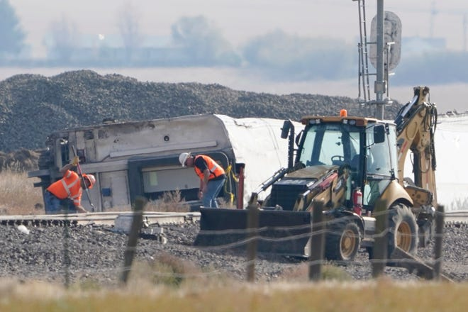 Workers stand near overturned cars from an Amtrak train on Monday, September 27, 2021, which derailed Saturday near Joplin, Mont., killing three people and injuring others.  Federal investigators are looking into the cause of the derailment.