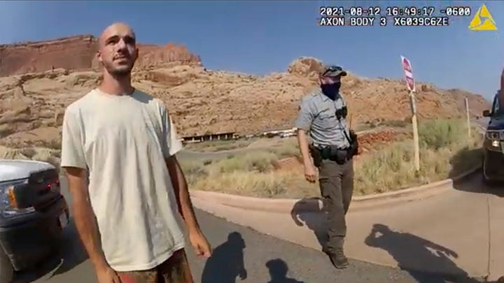 """This Aug. 12, 2021, photo from video provided by The Moab Police Department shows Brian Laundrie talking to a police officer after police pulled over the van he was traveling in with his girlfriend, Gabrielle """"Gabby"""" Petito, near the entrance to Arches National Park. Laundrie has been charged with unauthorized use of a debit card as searchers continue looking for him in Florida swampland, federal authorities announced Thursday, Sept. 23, 2021."""
