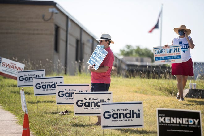 A volunteer with a judicial candidate's campaign is shown last year outside a Pflugerville election precinct, campaigning alongside signs for candidates for Congress and district attorney. Texas is one of six states that pick judges through partisan elections.