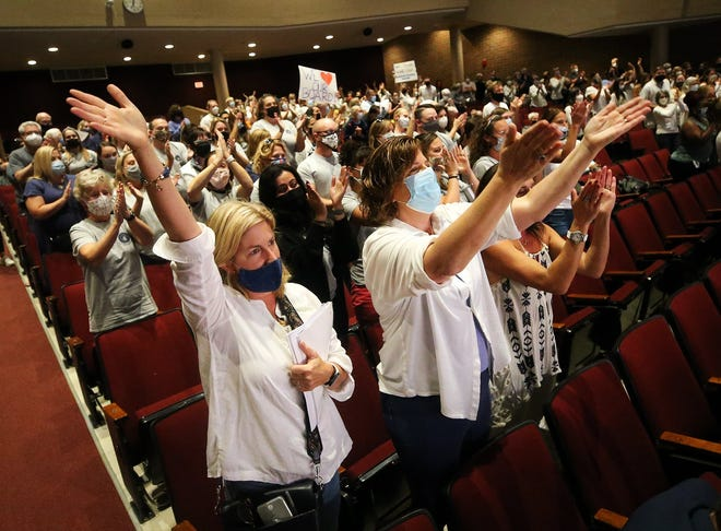 A large crowd of masked people stand in support of Hudson City School District board members at the beginning of a meeting Monday in the Hudson High School auditorium.